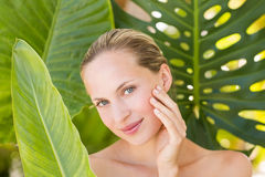 Beautiful blonde smiling at camera behind leaf Royalty Free Stock Images