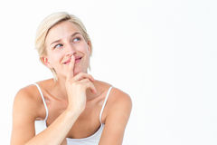 Beautiful blonde smiling with finger on mouth Stock Image