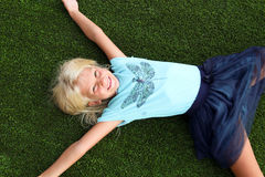 Beautiful blonde smiling  girl  sitting  on the grass on a summer day Stock Photography