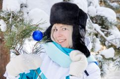 Beautiful blonde smiling girl in a warm fur hat on background of snowy fir-trees in winter stock photos