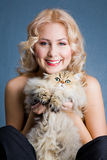 Beautiful blonde smiling woman with fluffy cat. Studio shot stock image
