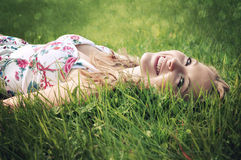 Beautiful blonde smiling woman lying in grass. Stock Photo
