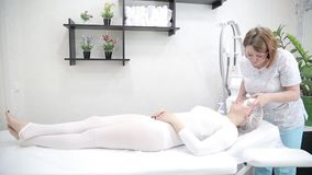 Removing wrinkles on the face and neck with massage. A beautiful blonde smooths wrinkles on the face and neck area with the help of LPG massage in the beauty stock video
