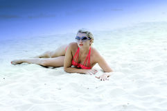 The beautiful blonde on snow-white sand in a lilac shade Stock Photography