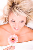 Woman with flower lying on towel Stock Images