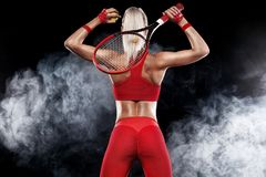 Beautiful blonde sport woman tennis player with racket in red costume. Beautiful girl tennis player with a racket on dark background wiht lights royalty free stock images