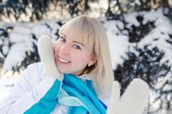 A beautiful blonde in sports clothes warms her cheek. With warm mittens in the forest against the background of snow-covered fir tree Royalty Free Stock Photos