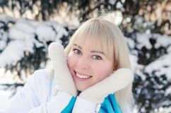 A beautiful blonde in sports clothes warms her cheeks. With warm mittens in the forest against the background of snow-covered fir tree Royalty Free Stock Photos