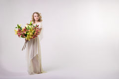 Beautiful blonde spring girl with big bouquet flowers Stock Photo