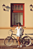 Beautiful blonde standing near her old bicycle. Outdoor fashion Royalty Free Stock Image
