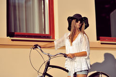 Beautiful blonde standing near her old bicycle. Outdoor fashion Stock Photos