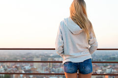 Beautiful blonde stands on the edge of the roof. Stock Photos