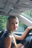 Beautiful blonde for steering wheel of the car Stock Image