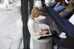 Beautiful blonde student with short hair sitting in a trendy bar in a lunch break, scans e-mail and makes business plan Stock Photo
