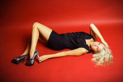 Beautiful blonde in a studio. Beautiful blonde in a black dress lying on a red background,  in a studio, fashion photography Stock Image