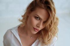 Beautiful blonde studio portrait. Beautiful seductive blonde wearing nice white shirt looking at camera studio portrait Royalty Free Stock Photos