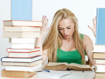 Beautiful blonde studying for an examination. Beautiful blonde being depressed while studying for an examination at her desk Stock Photo