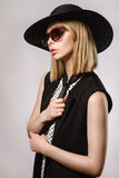 Beautiful blonde in sunglasses and hat keeps tie Royalty Free Stock Images