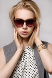 Beautiful blonde in sunglasses keeps hands near the face. Beautiful blonde keeps hands near the face on the gray background. Concept of the beauty Royalty Free Stock Photo