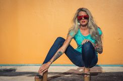 Beautiful blonde in sunglasses posing at the camera. Portrait on the background of bright orange wall. Modern hipster. Girl with tattoos. Sitting portrait stock image