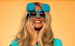 Beautiful blonde in sunglasses posing at the camera. Portrait on the background of bright orange wall. Modern hipster Stock Images