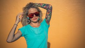 Beautiful blonde in sunglasses posing at the camera. Portrait on the background of bright orange wall. Modern hipster stock image