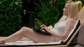 Beautiful blonde in swimsuit sitting on sun lounger and using laptop stock footage