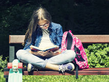 Beautiful blonde teen girl in jeans shirt reading a book on the bench with a backpack and skateboard in the park Stock Image