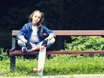 Beautiful blonde teen girl in jeans shirt, sitting on bench with backpack and skateboard in park Stock Images