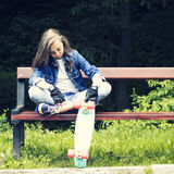 Beautiful blonde teen girl in jeans shirt, sitting on bench with backpack and skateboard in park Royalty Free Stock Images