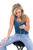 Beautiful Blonde Teen Girl Listening to Ipod. Teen girl sitting on stool listening to ipod.  Wearing jeans and decorative blue tank over white background Royalty Free Stock Photos