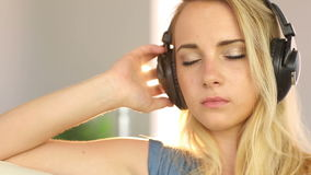 Beautiful blonde teen relaxing and listening to music Stock Image