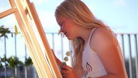 Beautiful blonde teenage girl paints a picture on the terrace.  stock video footage