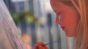 Beautiful blonde teenage girl paints a picture on the terrace.  stock footage