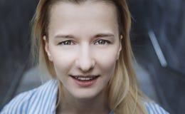 Beautiful blonde teenage girl smiling into camera. day royalty free stock photo