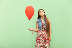 The beautiful blonde teenager dreaming, with red ballons on a green background. Royalty Free Stock Images