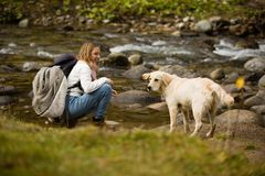 Beautiful blonde teenager girl with backpack in hiking bots and warm clothes, plays with her golden retriever friend outdoor, next stock photography