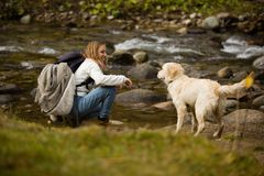 Beautiful blonde teenager girl with backpack in hiking bots and warm clothes, plays with her golden retriever friend outdoor. stock images