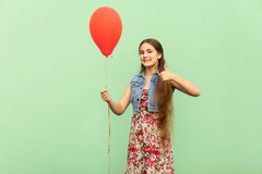 The beautiful blonde teenager with red ballons, thumbs up and toothy smile, on a green background. Stock Photography