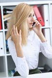 Beautiful blonde thoughtful businesswoman talk cellphone Royalty Free Stock Image