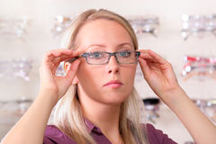 Beautiful blonde tries on glasses. Photo of the charming girl chooses the model of collets to glasses Royalty Free Stock Photo