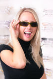 Beautiful blonde tries on glasses. Photo of the charming girl chooses the model of collets to glasses Stock Image