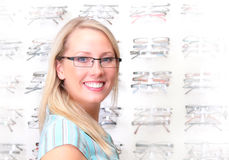 Beautiful blonde tries on glasses. Photo of the charming girl chooses the model of collets to glasses Royalty Free Stock Photos