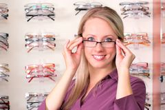 Beautiful blonde tries on glasses Royalty Free Stock Photo