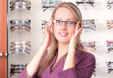 Beautiful blonde tries on glasses Royalty Free Stock Photography