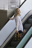 Beautiful blonde urban woman on city escalator. Color portrait of a beautiful young blonde city girl, wearing a short skirt and white shirt, standing on an Royalty Free Stock Photo