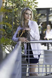 Beautiful blonde urban woman posing with handbag in city scene Royalty Free Stock Photo