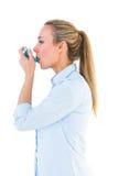 Beautiful blonde using an asthma inhaler Stock Photos