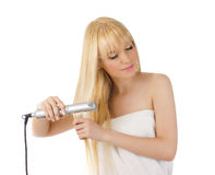 Beautiful blonde using hair straighteners Royalty Free Stock Image