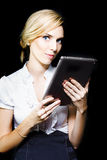 Beautiful blonde using a touch screen tablet. Beautiful stylish professional blonde woman holding a touch screen tablet with the screen facing herself and Royalty Free Stock Photo